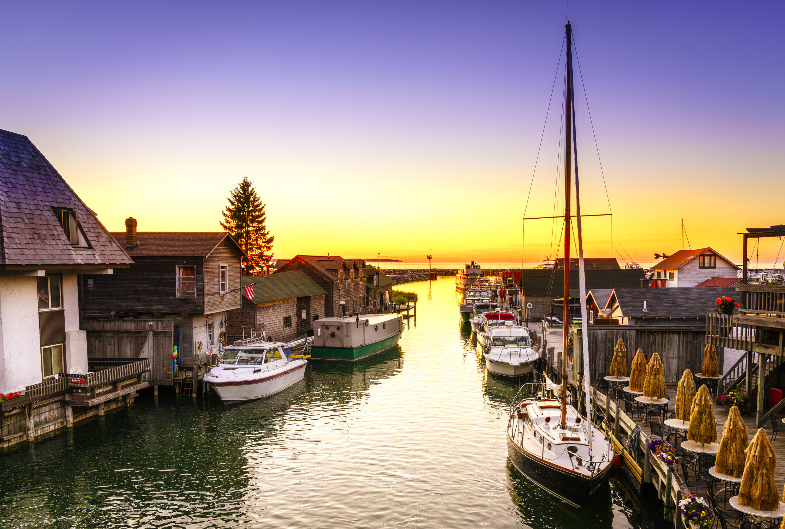 View of the sunset over Fishtown docks and boats on Lake Michigan in Leland, Michigan.