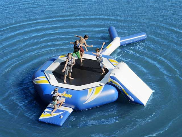 group of kids jumping on a playnorth watersports water trampoline rental in leelanau and grand traverse lake
