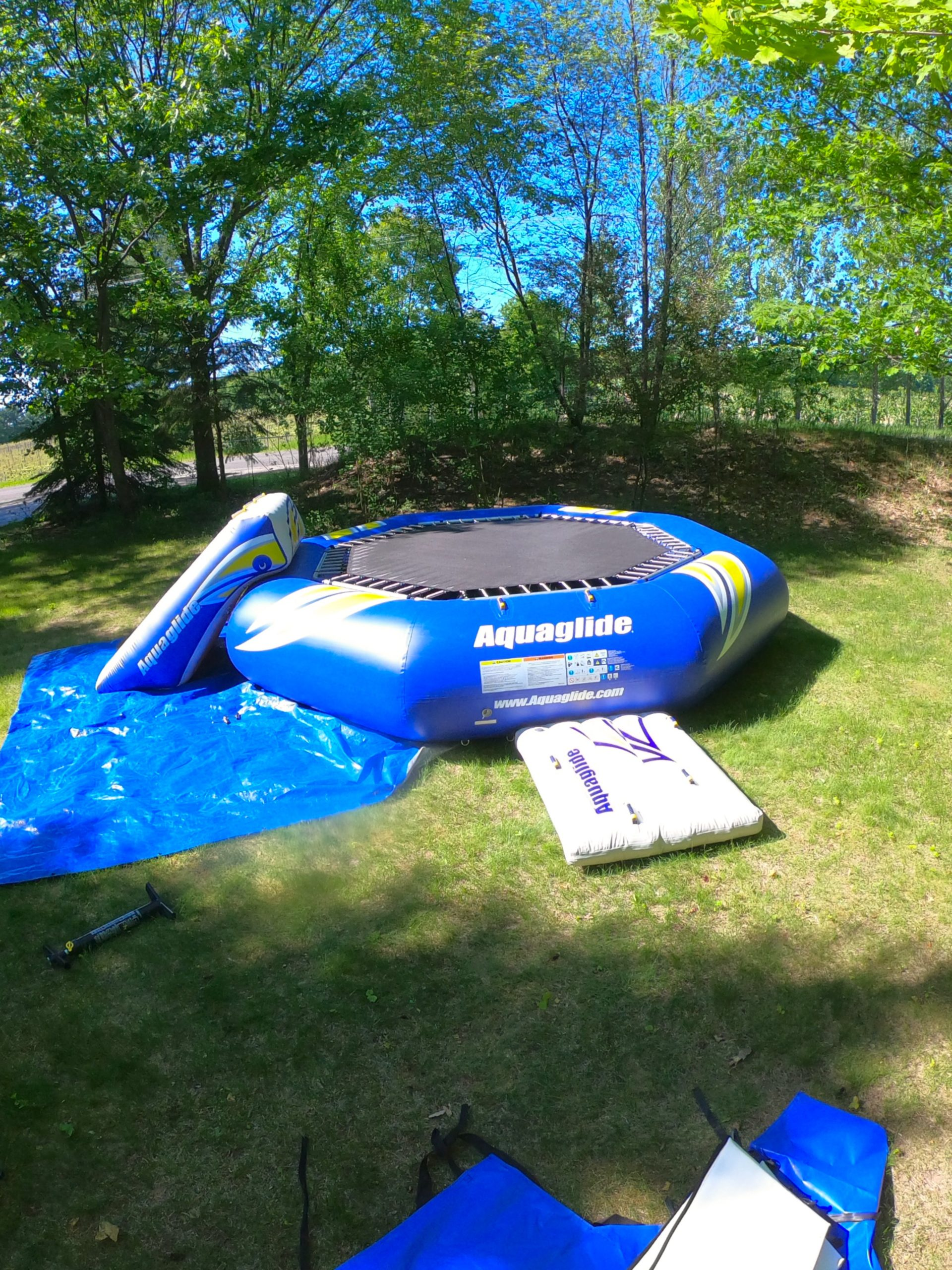 A PlayNorth water trampoline being set up with slide in leelanau county.